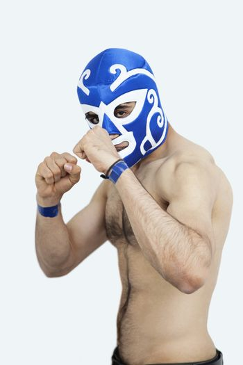 Portrait of a young shirtless male wrestler over gray background