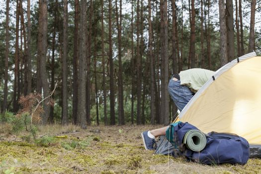 Low section of man entering tent in forest