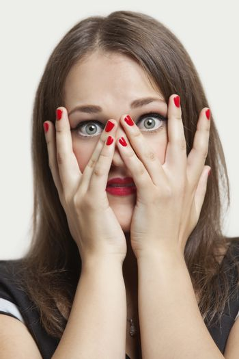 Portrait of young woman with gray eyes and red painted nails over gray background