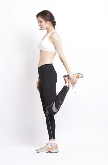 Young Asian woman in stretching against white background