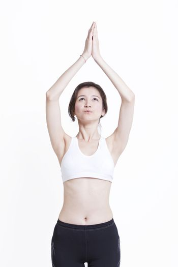 Young Asian woman with hands clasped practicing yoga against white background