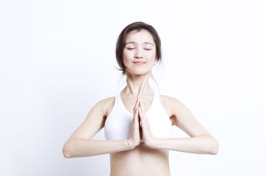 Young Asian woman in white sports bra meditating against white background