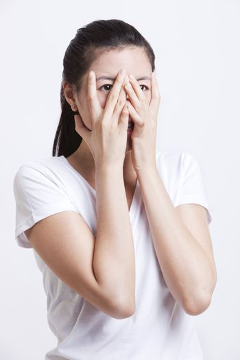 Frightened young woman with hands on face against white background