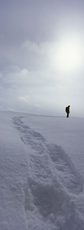 Person standing in winter landscape leaving behind trail of footprints
