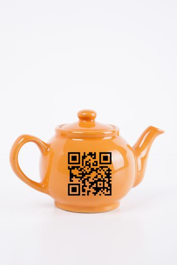 Close-up of orange kettle with barcode over white background