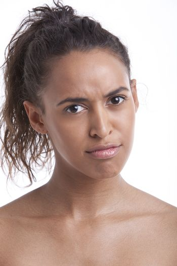 Portrait of young Mixed Race woman pouting against white background
