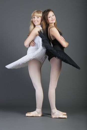 Portrait of two young female ballet dancers standing back to back over grey background