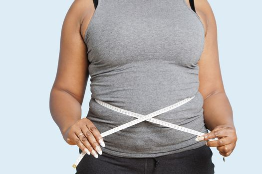 Mid section of woman measuring waist over blue background