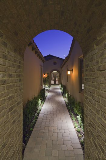 View through archway down path to French doors at dusk