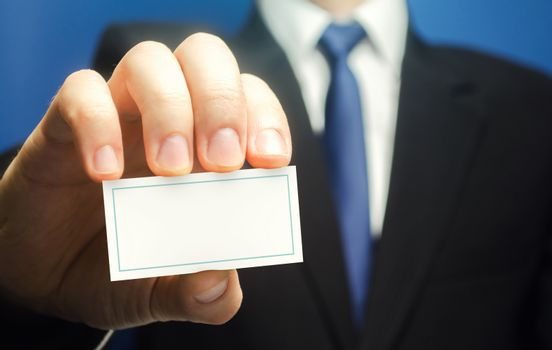 Businessman introduces himself with a business card. Presentation, hands over contacts to client. Agent offers his services. Solidity and style. Business advertising. Attracting new customers buyers.