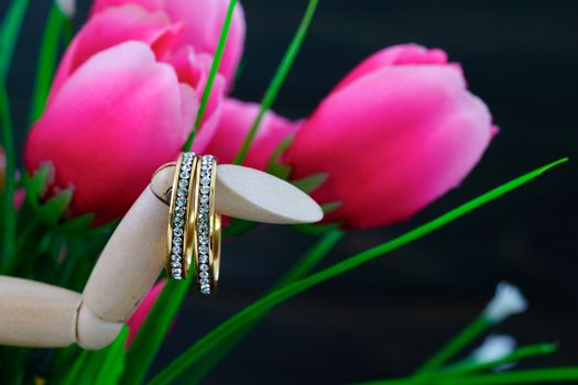 Diamond wedding ring resting in a fake pink tulip close up