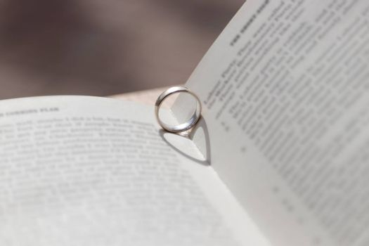 Romantic novel opened with ring giving heart shaped shadow