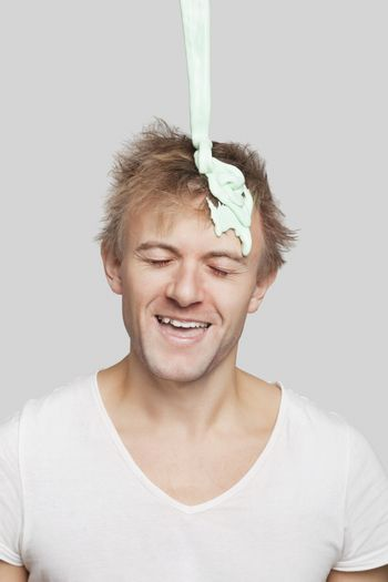Paint falling on young Caucasian man's head against gray background