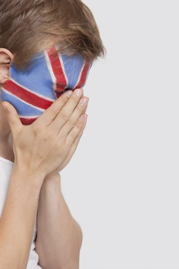 Sad young Caucasian man with British flag painted on face against white background