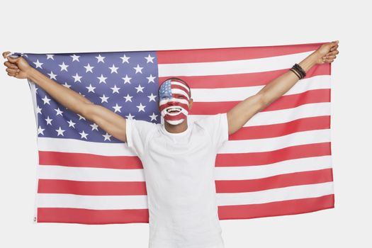 Portrait of Young man with American flag and painted face against white background