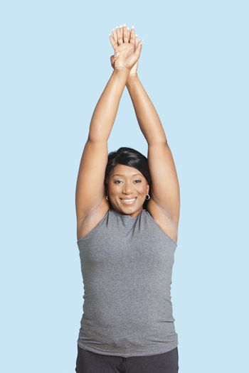 Portrait of mixed race woman stretching hands over blue background