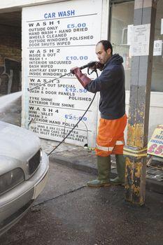 Employee washing vehicle at car wash