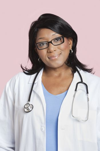 Portrait of mixed race female surgeon smiling over pink background