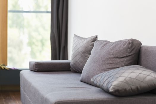 Gray sofa with cushions in house
