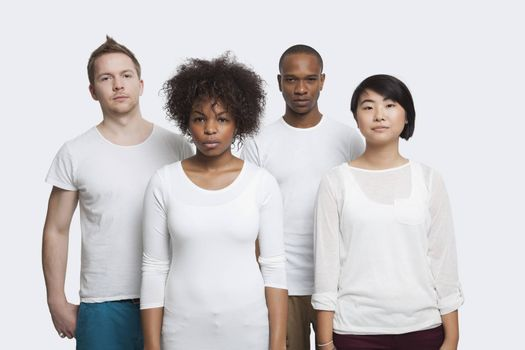 Portrait of young multi-ethnic friends in casuals standing together over white background