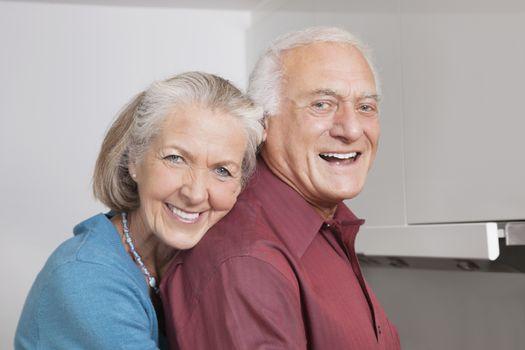Portrait of happy senior couple at domestic kitchen
