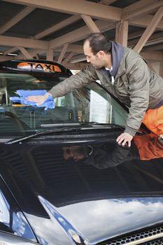 Employee wiping vehicle windscreen in car wash