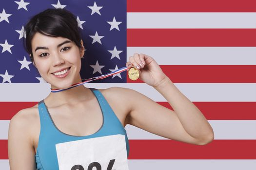 Portrait of smiling young female medalist standing against American flag