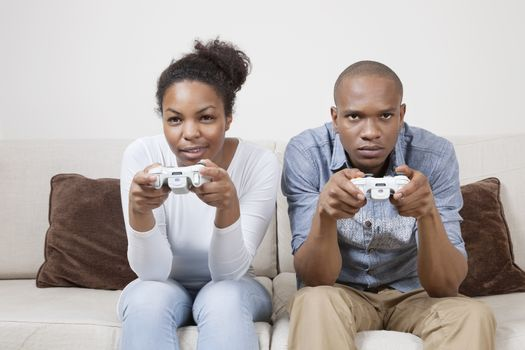 Portrait of young African American couple playing video game