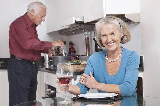 Portrait of happy senior woman with wine glass while husband cooking food in kitchen