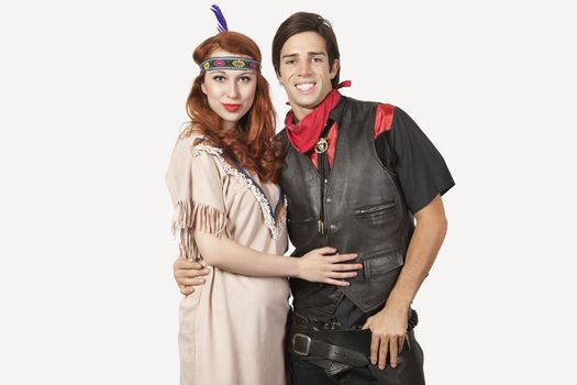 Portrait of young couple in old-fashioned costumes smiling against gray background