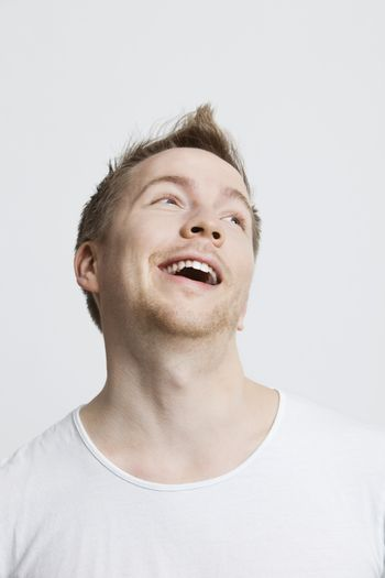 Young Caucasian man in white t-shirt day dreaming against white background