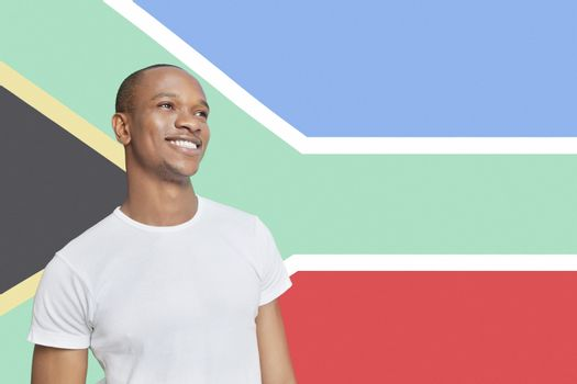 Young man in white t-shirt day dreaming against South African flag