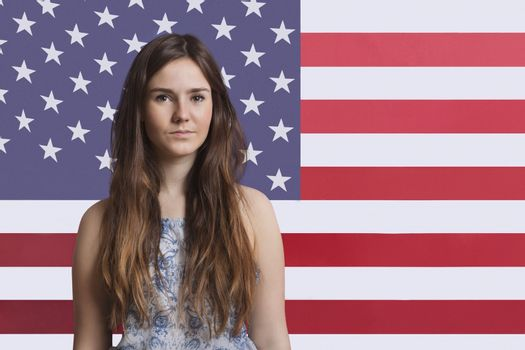 Portrait of young woman against American flag