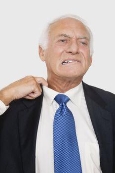 Elderly businessman holding collar feeling uncomfortable against white background