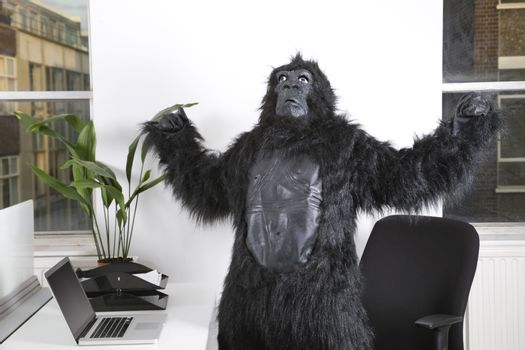 Angry young man in gorilla costume looking up at office