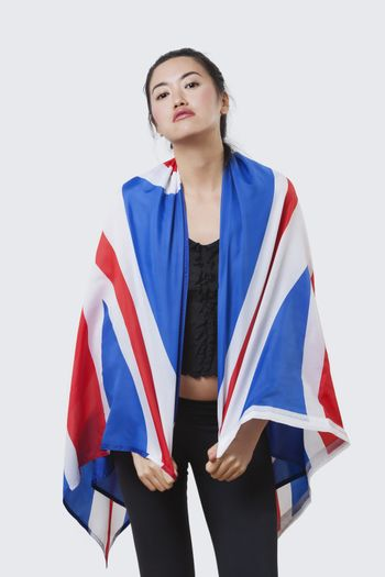 Patriotic young woman with British flag over white background