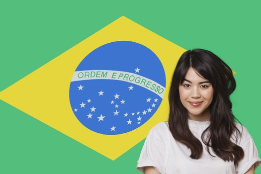 Portrait of smiling mixed race young woman against Brazilian flag