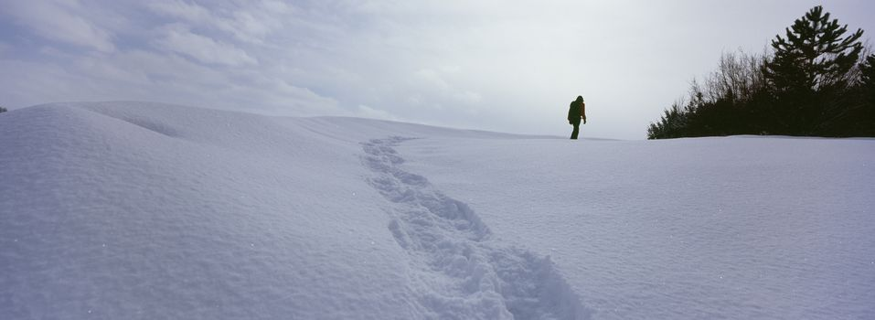 Person walking on snow covered land leaving behind trail of footprints