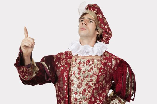 Young man in old-fashioned costume gesturing against gray background