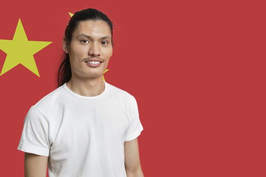 Portrait of young mixed race man standing against Chinese flag