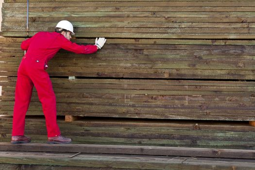 Hispanic worker inspecting timber wooden planks