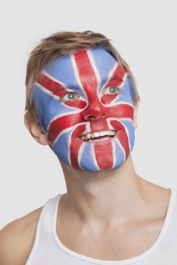 Young Caucasian man with British flag painted on face day dreaming against white background