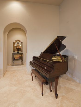 Baby grand piano in corner of luxury home