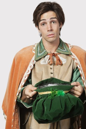 Portrait of young man in old-fashioned costume begging against gray background