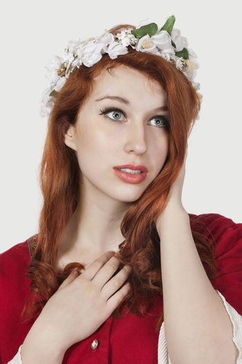 Beautiful young woman in old-fashioned princess costume looking away against gray background