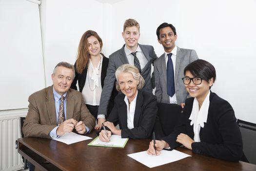 Portrait of happy multiethnic professionals meeting in office