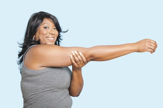 Portrait of mixed race woman stretching over blue background
