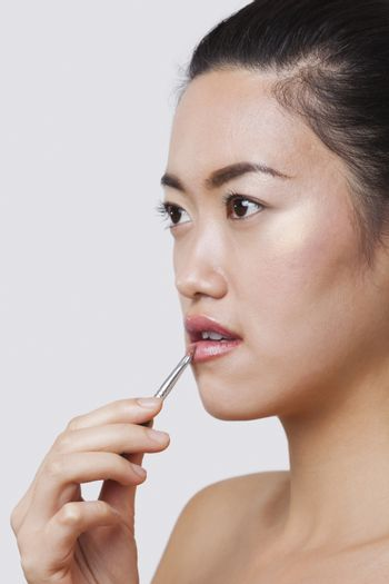 Close-up of young woman applying lip gloss with brush over white background