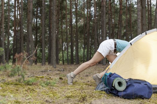 Low section of woman entering tent in forest