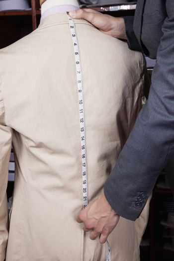 Hand measuring suit length with tape
